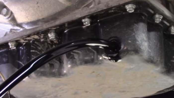 Drenando el aceite usado del carter hacia una bandeja recoge aceite 2