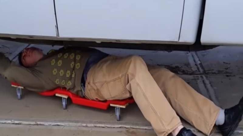 Hombre corpulento sobre una camilla de mecanico plastica