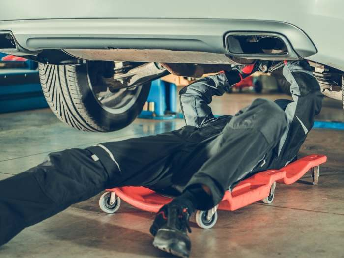 Hombre sobre una camilla mecanico reparando un coche