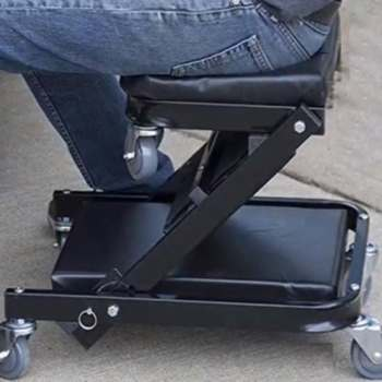 Mecánico sentado en una camilla de taller convertible a silla